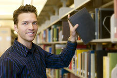 Man at library. Happy young man researching info at a library Royalty Free Stock Image