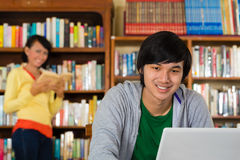 Man in library with laptop Royalty Free Stock Photo