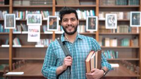 Man in the Library. Portrait of handsome intelligent student in the library, bearded asian man walking happily, holding books and black backpack, wearing blue stock footage