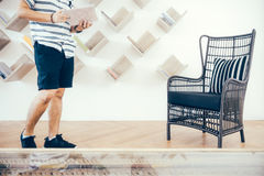 Man in the Library. A man is searching for the book he wants in a beautifully decorated library with a bookshelf and rattan chair Stock Photo