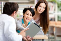 Man at the library shows tablet to two women Stock Images