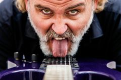 Man licking his electric guitar with the tongue Royalty Free Stock Photos