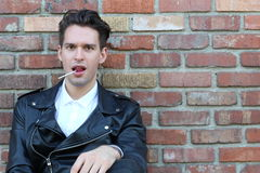 Man licking a pink shiny lollipop. Close up against red brick wall background Royalty Free Stock Photos