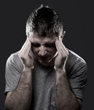Man lidandemigränhuvudvärken smärtar in känsligt sjukt med händer på tempo Royaltyfria Bilder