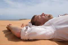 Man lie alone in the sunny desert. He is lost and out of breath. No water and energy. Concept for depression and noway situation in life Royalty Free Stock Images