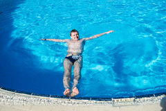 Man lie on surface of water in the swimming pool Stock Images