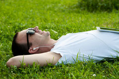 Man lie with tablet on the grass. Man lie on the grass with tablet in the park and listening to music Royalty Free Stock Photos