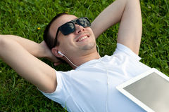 Man lie with tablet on the grass Stock Photo