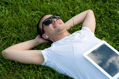 Man lie with tablet on the grass Stock Images