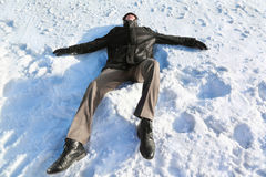 Man lies on back by winter day. And rests closing eyes Royalty Free Stock Photo