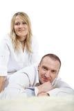 Man lies on carpet, woman sits near Royalty Free Stock Photography