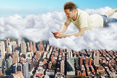 Man lies on clouds with smartphone above megapolis city concept Royalty Free Stock Photo
