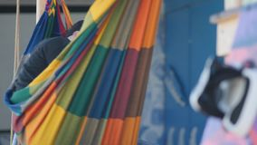 A man lies in a colored hammock, next to a board for kite