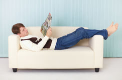 Man lies comfortably on sofa with a magazine Royalty Free Stock Image