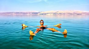 Man lies in the dead sea. Jordan on a background royalty free stock photo