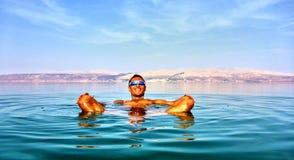 Man lies in the dead sea. Jordan on a background stock photos