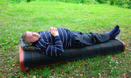A man lies on a mattress Royalty Free Stock Photos