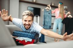 Man lies on overfilled suitcase, fees on journey. Man lies on overfilled suitcase, overflowing or overloaded suitcase. Fees on journey concept. Luggage stock images