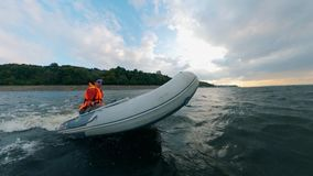 A man in life jacket sailing inflatable boat on water. HD stock footage