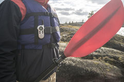 Man in a life jacket with a walkie-talkie and a paddle standing Royalty Free Stock Photography