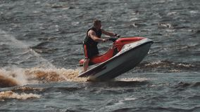 Man in life vest riding on a jet ski on hight speed makes extreme turns stock video