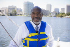 Man in Life Vest on Sailboat Stock Photo