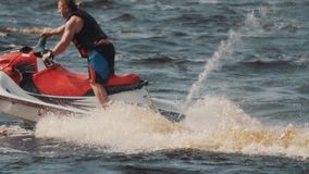 Man in life vest showing extreme turns and twists on a jet ski on hight speed
