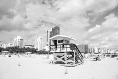 Man lifeguard patrolling beach on wooden tower. Miami, USA - January 10, 2016: man or male lifeguard patrolling beach on wooden tower on sunny day with high Royalty Free Stock Images