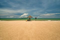 A man lifeguard, sitting under an umbrella of palm leaves on a deserted beach of Hainan Island. The tropical island of Hainan is located in the south of China stock photos