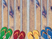 Man lifestyle six relax flip flops on sandy beach wooden path. Close Royalty Free Stock Images