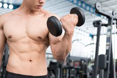 Man lift dumbbell in gym. bodybuilder male working out in fitnes Royalty Free Stock Photo