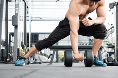 Man lift dumbbell in gym. bodybuilder male working out in fitnes. Young man lift dumbbell in gym. bodybuilder male working out in fitness center. sport guy doing Royalty Free Stock Photography