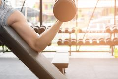 Man lift dumbbell in gym. bodybuilder male working out in fitnes. Young man lift dumbbell in gym. bodybuilder male working out in fitness center. sport guy doing Royalty Free Stock Images