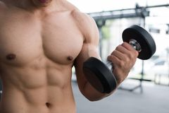 Man lift dumbbell in gym. bodybuilder male working out in fitnes. Young man lift dumbbell in gym. bodybuilder male working out in fitness center. sport guy doing Royalty Free Stock Image