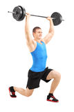 Man lifting a barbell and doing lunges Royalty Free Stock Images