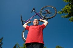 Man Lifting Bicycle Over Head Smiling - horizontal Stock Images