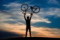 Man lifting bicycle at sunset sky. Silhouette of man lifts bicycle standing on hill on evening sky background. Enjoy your life Stock Photo