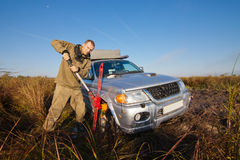 Man lifting car stucked in deep mud by hi jack Stock Image