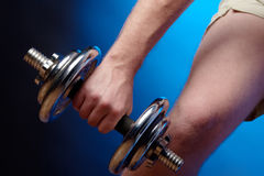 Man lifting a dumbbell. Man working out with a metal dumbbell Royalty Free Stock Photos