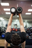 Man lifting dumbbell weights while lying down Royalty Free Stock Photography