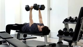 Man lifting dumbbells lying on bench stock video footage