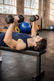 Man lifting dumbbells lying on exercise bench. At the gym Stock Images