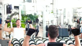 Man lifting dumbbells sitting on front of mirror. stock video footage
