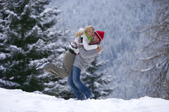 Man lifting girlfriend in snow on remote snowy hillside Royalty Free Stock Photo