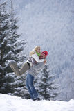 Man lifting girlfriend in snow on remote snowy hillside Stock Photography