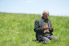 Man lifting hands in prayer. Senior man lifting hands in prayer on grassy hill royalty free stock image