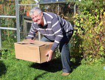 Man lifting heavy box correctly. An elderly man lifting a heavy box correctly and getting no back pain Stock Photo