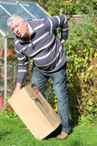 Man lifting heavy box and getting back pain. An elderly man lifting a heavy box incorrectly causing him bad back pain Stock Photos