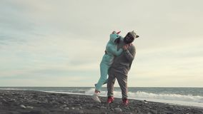 Man is lifting his girlfriend, both in kigurumi and standing on beach near sea. Woman and man is having fun on a pebble beach in evening. They are wearing funny stock footage
