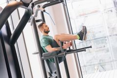 Man lifting his legs up on a gym machinery. Young active man lifting his legs up on a special gym machinery. Fit lifestyle Stock Images